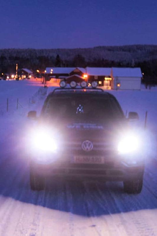 Ein Amarok mit leuchtenden Scheinwerfern fährt abends eine verschneite Straße entlang.