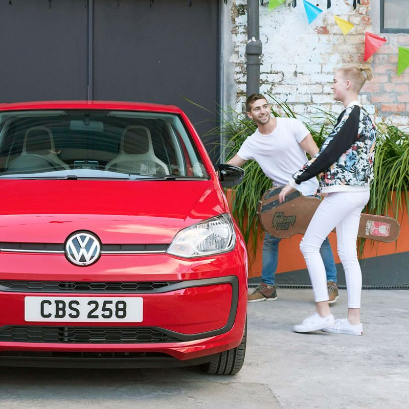 A young group getting into a red Volkswagen up!