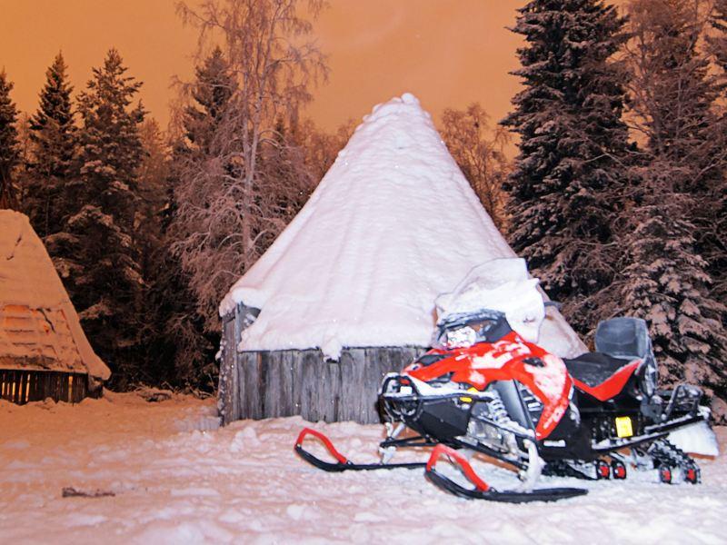 Vor zugeschneiten Waldhütten steht ein Schneemobil.