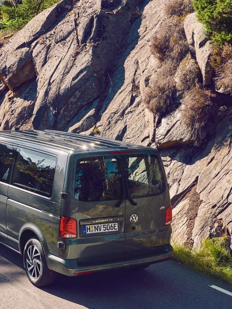 Une Volkswagen Caravelle roule sur une route de montagne.