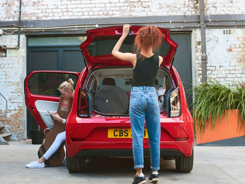 A lady opening the boot of a red Volkswagen up!, her friend in the passenger seat on her phone.