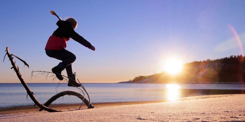Ein Mädchen in Winterkleidung macht am Strand einen Luftsprung.