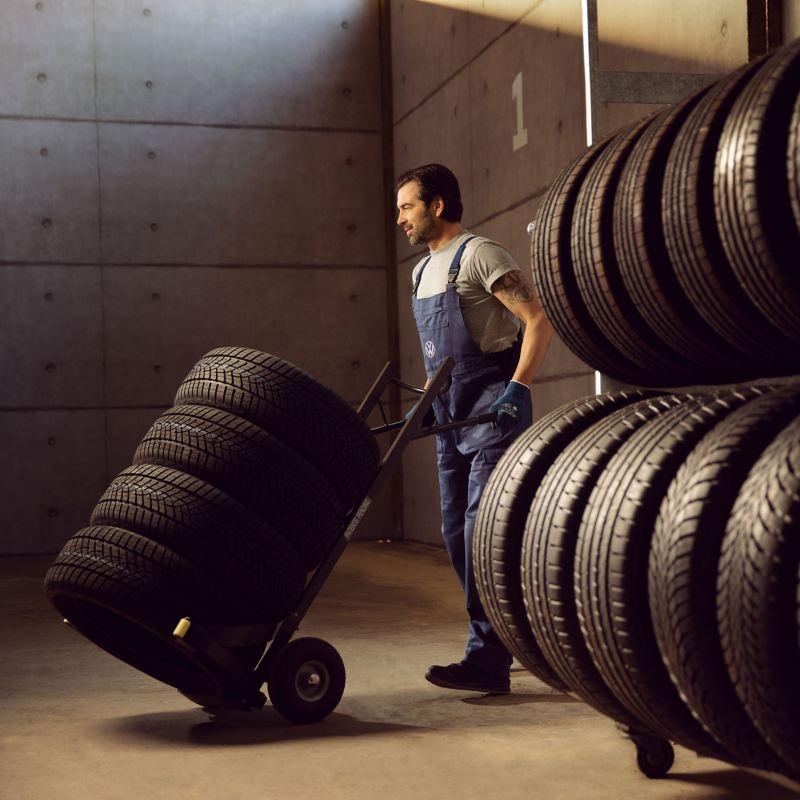 Ein VW Servicemitarbeiter transportiert einen Satz Reifen