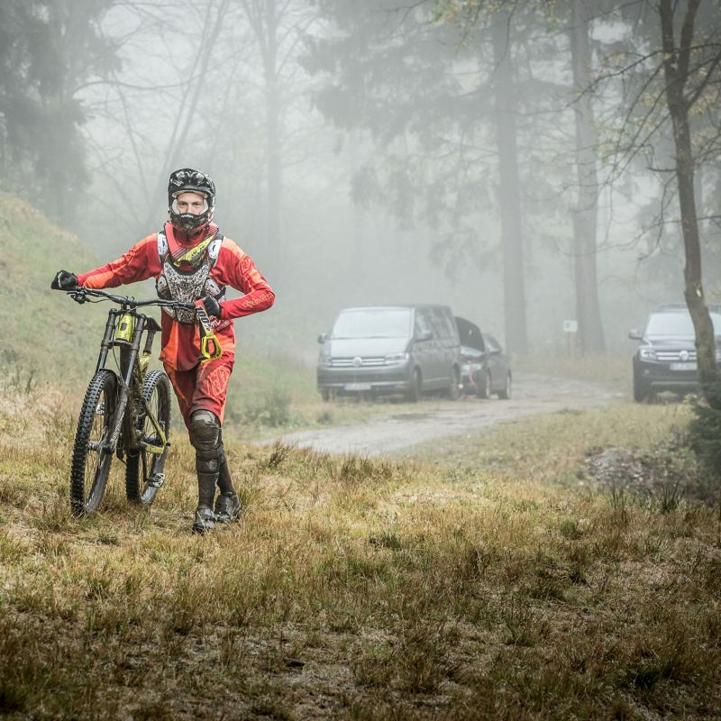 Christian Junker starts his mountain bike tour, in the background are several parked VW cars