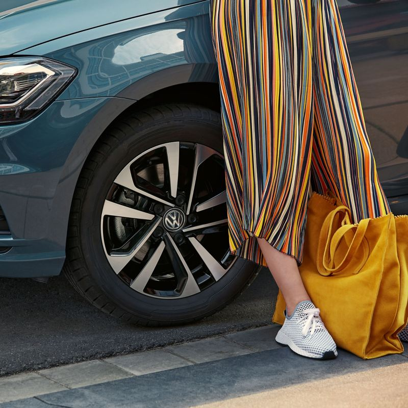 A woman with a yellow bag leans against her blue VW vehicle with a wheel/tyre combination for the summer