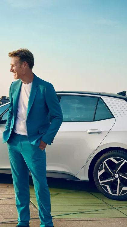 A man in a light blue suit standing in front of a Glacier White Metallic Volkswagen ID.3 1st Edition