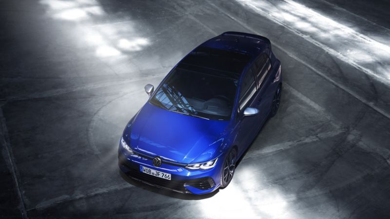 A ¾ high angle shot looking down on a bold, blue coloured 2022 Golf R. It's parked on grey asphalt with tire marks visible.