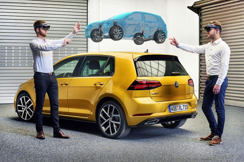 Due specialisti vicino ad una Golf Volkswagen progettano un modello di auto grazie ad un visore per la realtà aumentata