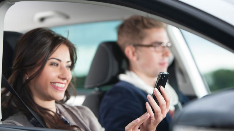 ragazza in auto che legge lo smartphone
