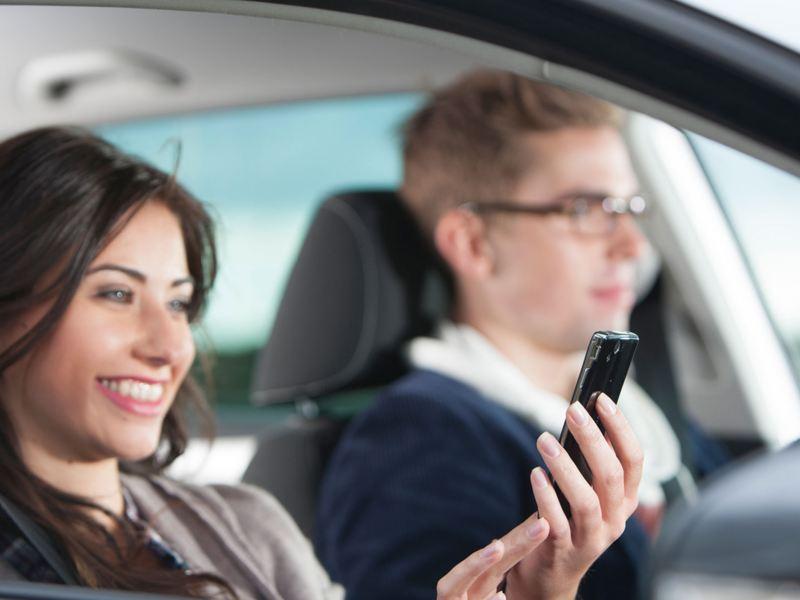 Un uomo e una donna a bordo di un veicolo Volkswagen, lui guida, lei sorride guardando lo smartphone.