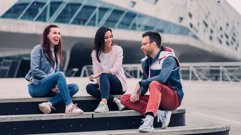 Two young women and a young man sitting on steps