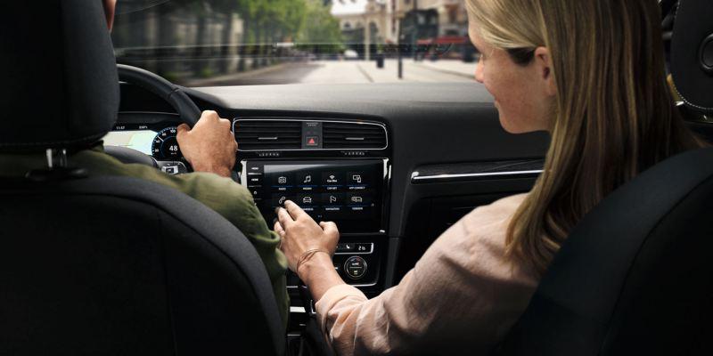 Pareja dentro de un Volkswagen Golf, la mujer controla la pantalla interactiva