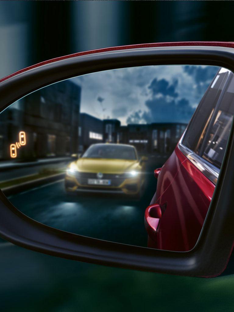 Retrovisor de un Golf Sportvan rojo avanzando en la noche con el detector de ángulo muerto activo