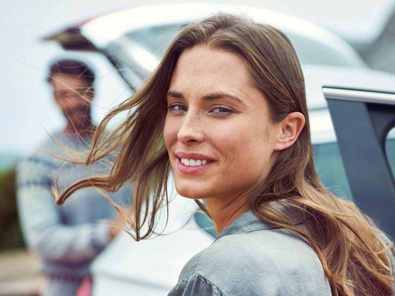 Chica con pelo largo girándose para mirar a la cámara mientras avanza hacia su Volkswagen
