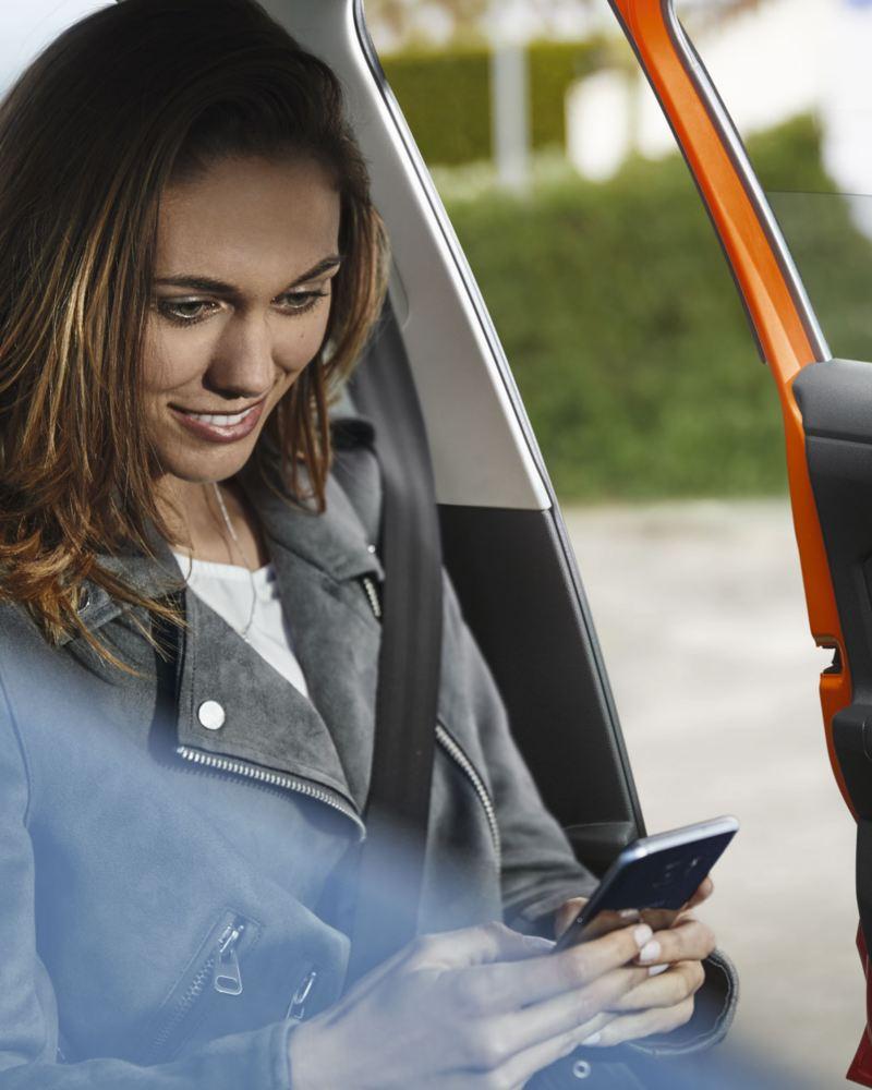 Chica mirando mirando el móvil dentro de un Volkswagen Polo con la puerta abierta