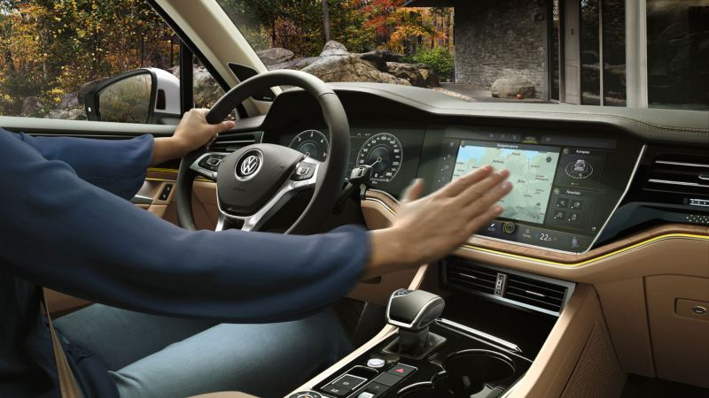Hombre al volane de un Volkswagen Touareg usando el sistema de navegación Discover Premium