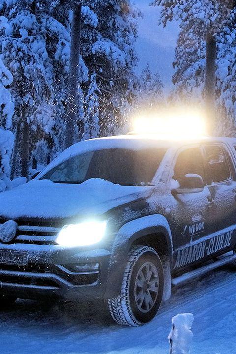Der Volkswagen Nutzfahrzeuge Amarok fährt bei Dämmerung durch eine verschneite Winterlandschaft.