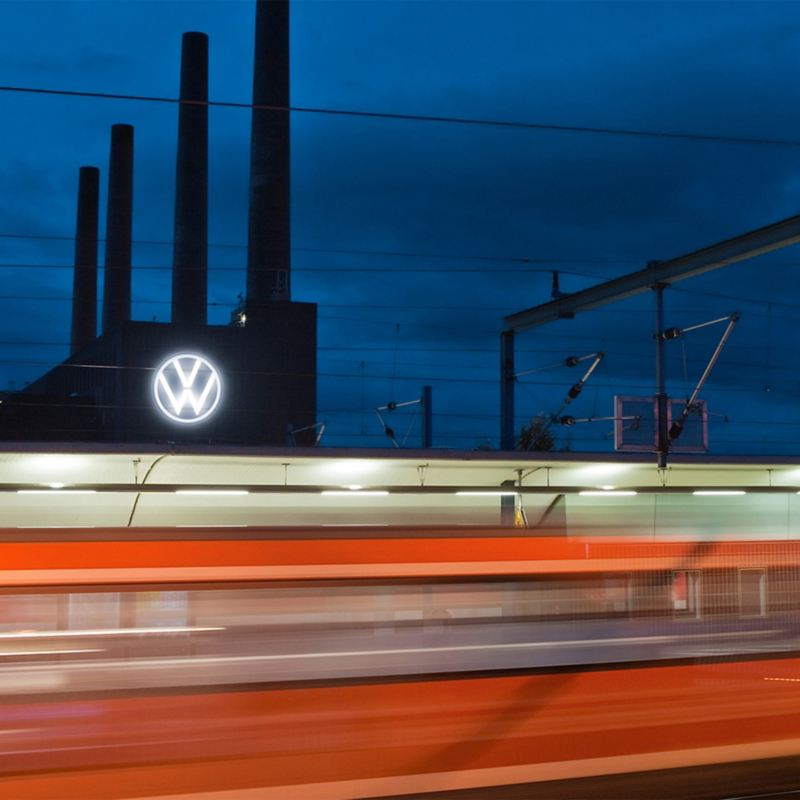 A moving train and the Volkswagen plant in Wolfsburg at night in the background