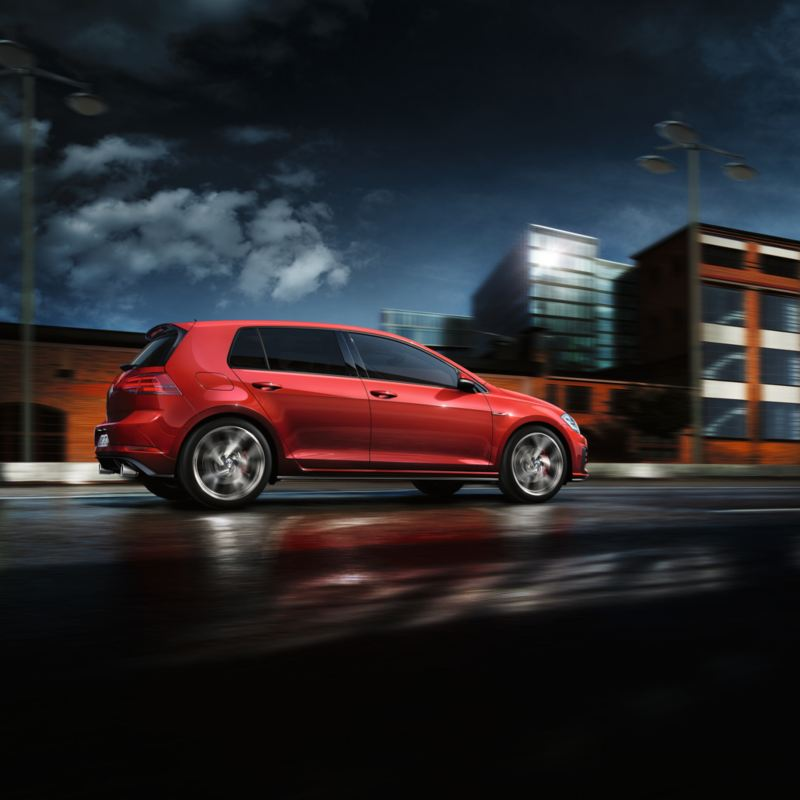 Vista lateral de un Golf GTI rojo acelerando por la calle de una ciudad