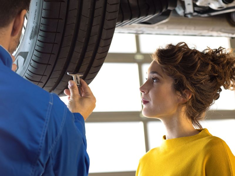 Chica con un jersey amarillo mirando cómo un mecánico de Volkswagen repara un neumático