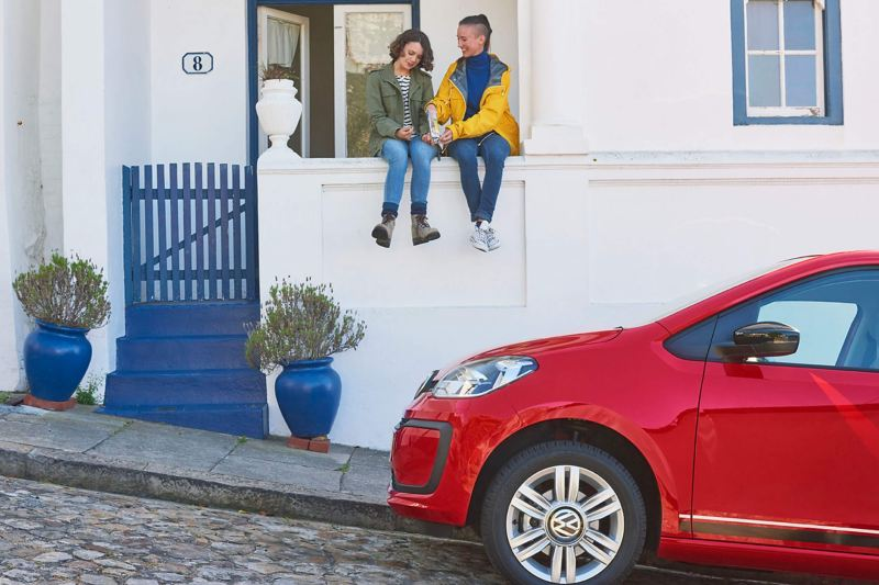 A young couple sat on the wall of a house on a steep street, a red Volkswagen up! parked on the cobbled road.