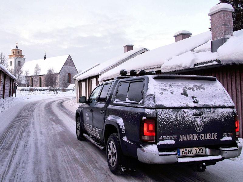 Wir sehen den Amarok von hinten. Er fährt durch ein verschneites Dorf.