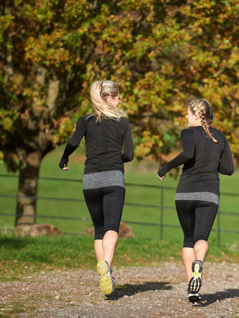 Two women jogging together in an autumnal landscape