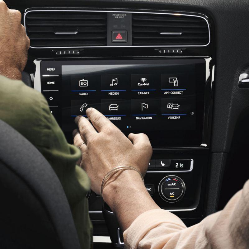 Mano utilizando la pantalla táctil del dispositivo We Connect de un Volkswagen
