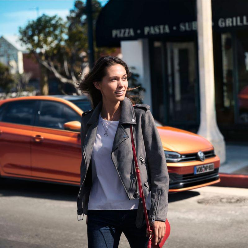 Chica mirando hacia un lado mientras avanza dejando atrás un Volkswagen Polo