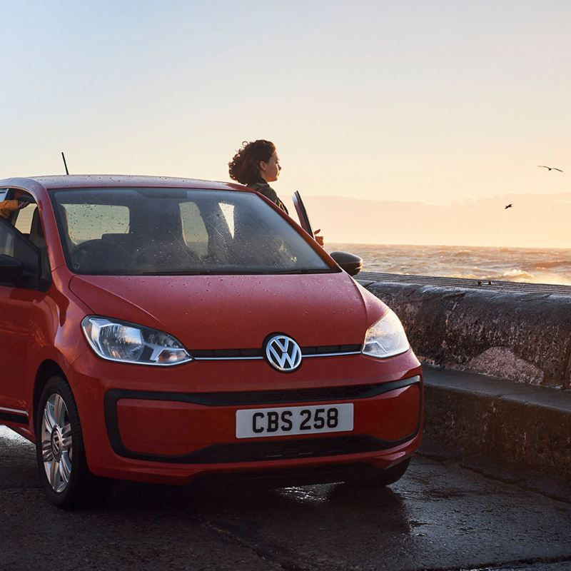 A couple getting out of a red Volkswagen up! on a coastal promenade.