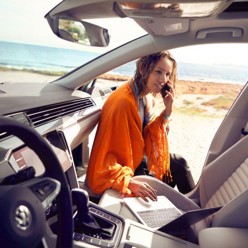 Mujer sentada en un Passat Alltrack con la puerta abierta usando un ordenador portátil y hablando por móvil