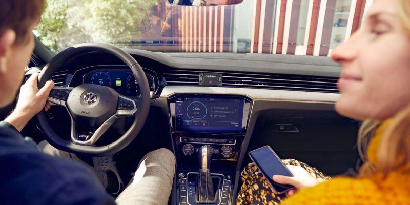Hombre joven visto desde atrás al volante de un Volkswagen Passat, lo acompaña una chica con un móvil en la mano