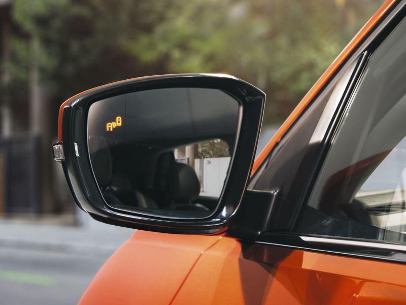 Detector de ángulo muerto en el retrovisor de un Volkswagen T-Cross naranja