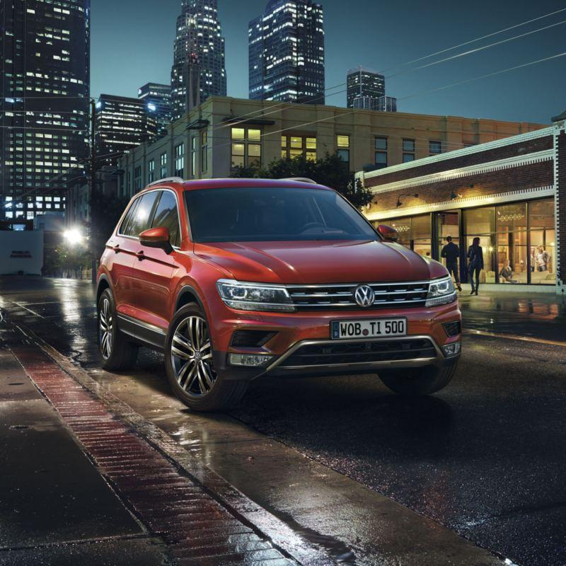 Volkswagen Tiguan rojo circulando por una ciudad de noche