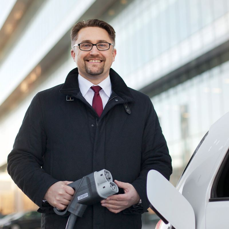 A man standing with a charging connector next to an electric vehicle