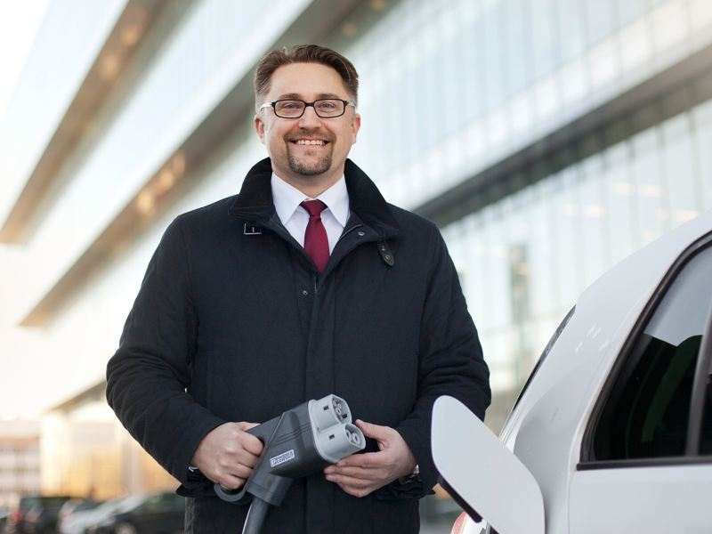 A man standing with a charging cable next to an electric vehicle