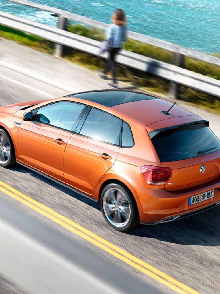 Volkswagen Polo naranja subiendo la pendiente de una carretera junto al mar