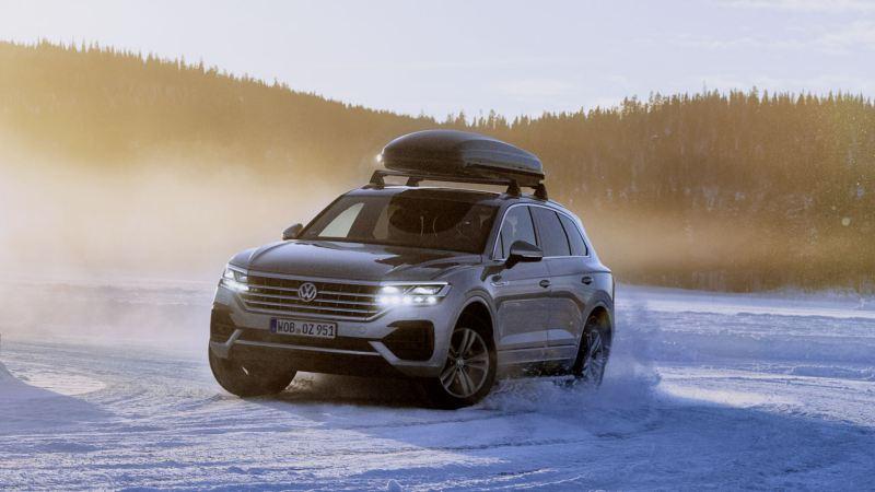 Volkswagen Touareg con un baúl de techo circulando por la nieve