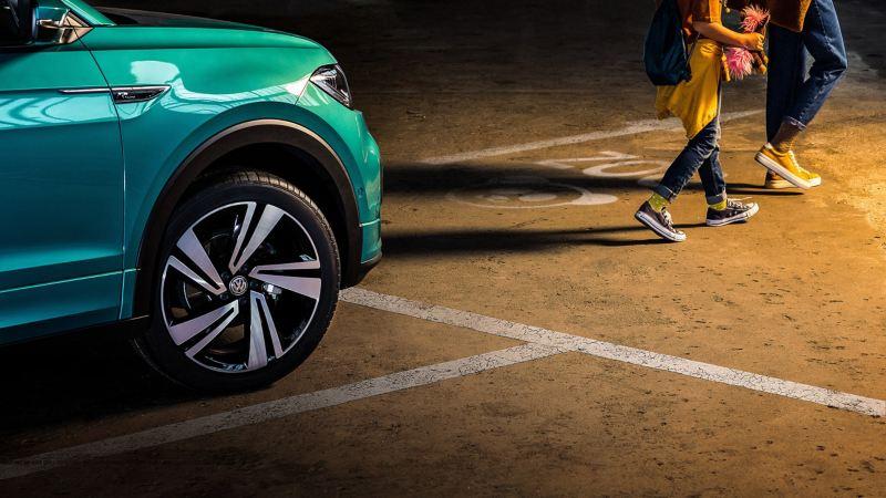 Dos personas se alejan de su vehículo Volkswagen estacionado con neumáticos AirStop®