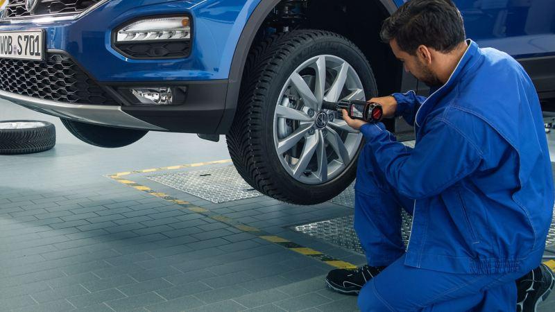 Addetto Volkswagen service agisce su uno pneumatico