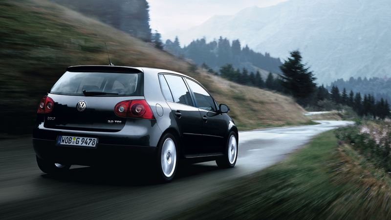 Une VW Golf 5 2.0 TDI noire avec des pneus toute saison roule sur la route