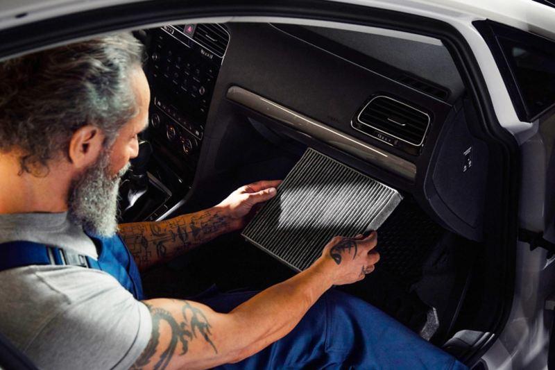 Un addetto VW Service intento a cambiare il filtro antipolline dell'abitacolo di una Volkswagen.