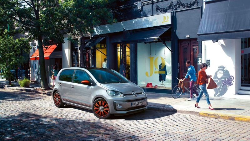 A silver VW up! with natural gas using in a city