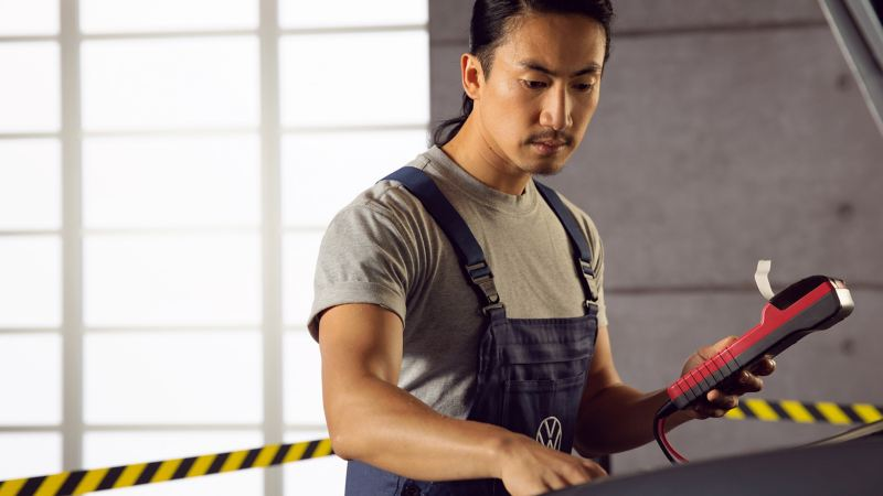 A VW service employee during inspection works on a VW EV
