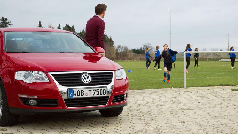 Ein Vater wartet am Familienauto auf seine Tochter, die gerade vom Fußballtraining kommt – VW Passat B6