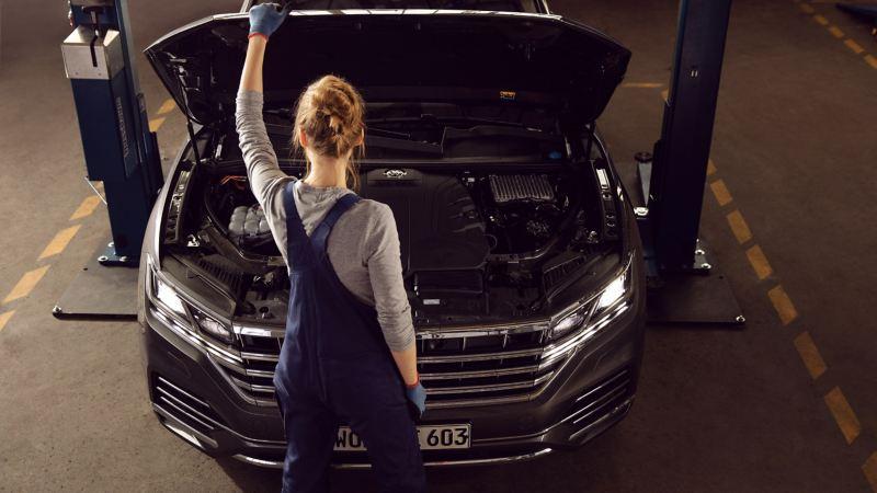 Phụ tùng thay thế: Nhân viên dịch vụ VW thay má phanh cho chiếc VW màu vàng