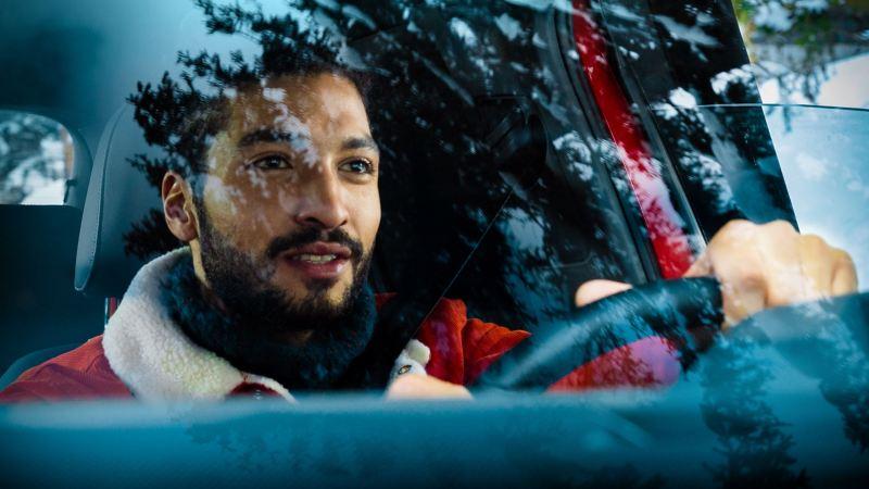 Một người đàn ông lái chiếc xe VW màu đỏ đang nhìn ra ngoài cửa kính