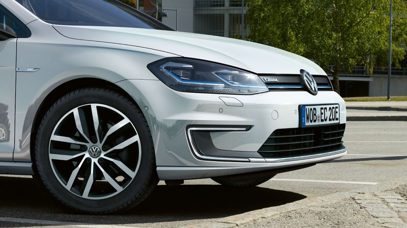 A white VW e-Golf parks on the road and is ready for the warm season – Volkswagen summer wheels and tyres
