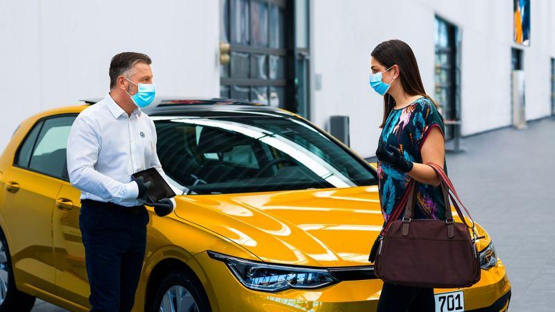 Una donna parla con un addetto in un centro Volkswagen Service.