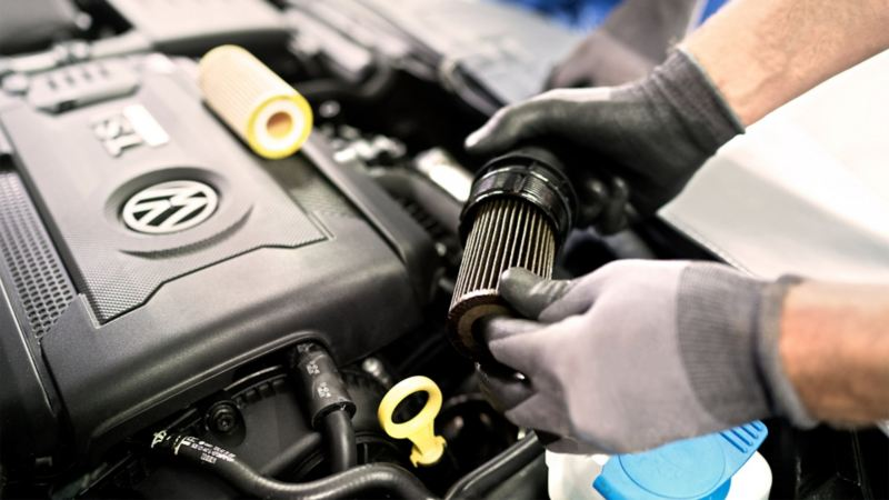 Un addetto VW Service sta cambiando il filtro dell'aria di una Volkswagen.